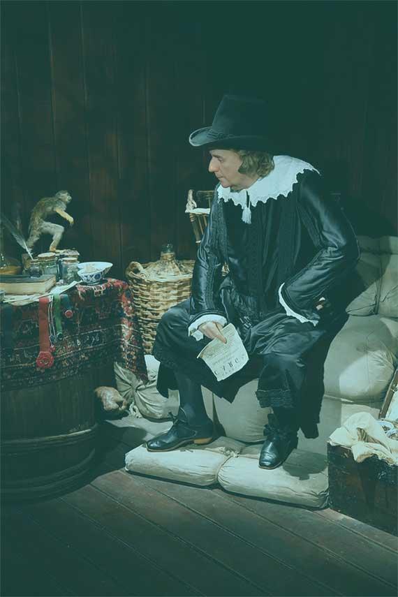 Historischer Kaufmann der auf Säcken sitzt